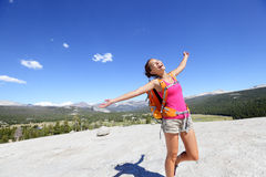 Happy hiking woman dancing in mountain landscape. Young asian adult doing funny freedom pose on top of the Pothole Dome in Yosemite National Park, California Stock Photo
