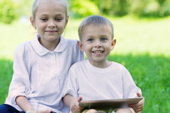 Happy hildren use a tablet pc Stock Photo