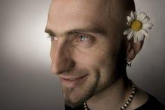 Happy Hippie. Man with ox daisy over ear Stock Photos
