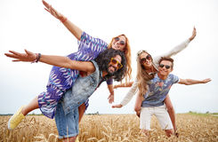 Happy hippie friends having fun on cereal field. Nature, summer, youth culture and people concept - happy young hippie friends having fun on cereal field Royalty Free Stock Photo