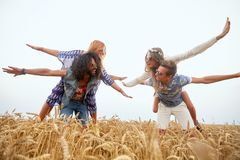Happy hippie friends having fun on cereal field Stock Photos