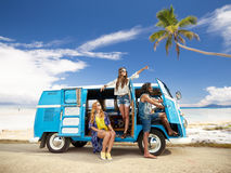 Happy hippie friends in minivan car on beach. Summer holidays, road trip, travel and people concept - smiling young hippie friends in minivan car over tropical Stock Images