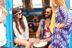 Happy hippie friends playing music in minivan. Summer holidays, road trip, travel and people concept - happy young hippie friends with tom-tom drum having fun Stock Photography