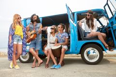 Happy hippie friends playing music in minivan Royalty Free Stock Image