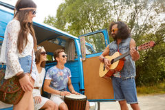 Happy hippie friends playing music in minivan Royalty Free Stock Images