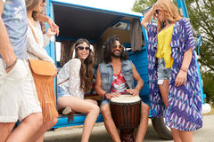 Happy hippie friends playing music in minivan. Summer holidays, road trip, travel and people concept - happy young hippie friends with tom-tom drum having fun Royalty Free Stock Image