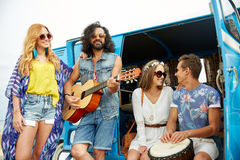Happy hippie friends playing music over minivan Royalty Free Stock Photography