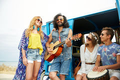 Happy hippie friends playing music over minivan. Summer holidays, road trip, vacation, travel and people concept - happy young hippie friends having fun and Royalty Free Stock Image