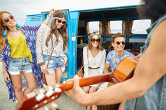 Happy hippie friends playing music over minivan Stock Photo