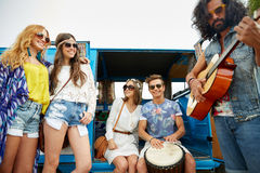 Happy hippie friends playing music over minivan Royalty Free Stock Photo