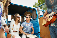 Happy hippie friends playing music over minivan. Summer holidays, road trip, vacation, travel and people concept - happy young hippie friends having fun and Stock Images