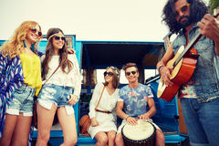 Happy hippie friends playing music over minivan Royalty Free Stock Images