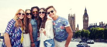 Happy hippie friends with selfie stick at coliseum. Summer vacation, travel, tourism, technology and people concept - smiling young hippie friends taking picture stock photo