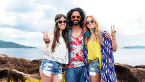 Happy hippie friends showing peace on summer beach Stock Photography