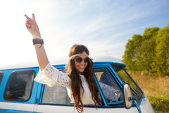 Happy hippie woman showing peace in minivan car. Summer holidays, road trip, travel and people concept - smiling young hippie woman showing peace gesture in Stock Photo