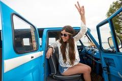 Happy hippie woman showing peace in minivan car Stock Photo