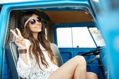 Happy hippie woman showing peace in minivan car. Summer holidays, road trip, vacation, travel and people concept - smiling young hippie woman showing peace Stock Images