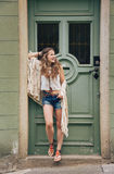 Happy hippy-looking woman standing outdoors against wooden door Royalty Free Stock Photos