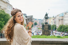 Happy hippy-looking woman tourist  with retro camera  in Prague Stock Photo