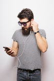 Happy Hipster with beard wearing shirt and sunglasses enjoying music. Against white background royalty free stock photo