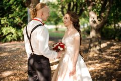 Happy hipster bride and groom walking in the forest. Among green trees on warm summer day royalty free stock images