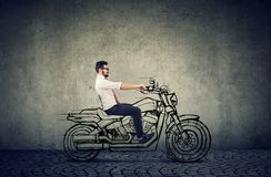 Happy hipster business man riding a motocycle. Happy hipster young business man riding a motocycle feeling happy royalty free stock photos