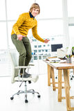 Happy hipster businessman standing on his chair Stock Photo