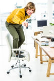 Happy hipster businessman standing on his chair Stock Image