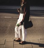 Happy hipster carefree girl in boho outfit with flowers relaxing in evening light in summer city. Stylish bohemian girl walking in. Sunny street. Space for text stock images