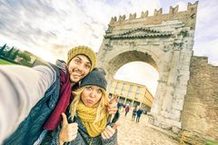 Happy hipster couple taking selfie at european city trip. On winter clothes - Fun concept with alternative fashion world travelers royalty free stock images