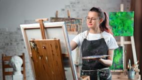 Happy hipster creative female painter enjoying drawing picture on canvas at art studio medium shot. Smiling artist woman in apron painting easel using color stock video footage