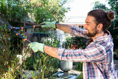 Happy hipster cutting hedges with clippers at garden Stock Photos