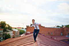 Happy hipster on the edge of the roof Royalty Free Stock Images