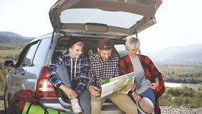 Happy hipster friends are looking at the road map while sitting in front of the travel car trunk with the smile. Friends