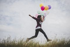 Happy hipster girl jumping with colorful toy balloons outdoors. stock images
