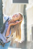 Happy hipster girl listening music on city street Stock Photography