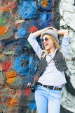 Happy hipster girl looking on copy space against urban wall Stock Photo