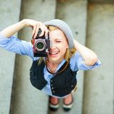 Hipster girl making photo with retro camera on city street Stock Image