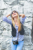 Happy hipster girl rejoicing against rocky wall outdoors Stock Images