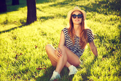 Happy Hipster Girl Relaxing on the Grass. Toned and Filtered Photo. Modern Youth Lifestyle Concept Stock Images
