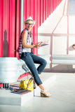 Happy hipster girl sitting on street and holding notebook Royalty Free Stock Images