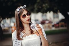 Happy hipster girl with sunglasses, in retro dress and headband, holding plastic cup and straw, drinking lemonade. Beautiful. Stylish young woman holding drink royalty free stock image