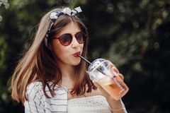 Happy hipster girl with sunglasses, in retro dress and headband, holding plastic cup and straw, drinking lemonade. Beautiful. Stylish young woman holding drink royalty free stock images