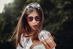 Happy hipster girl with sunglasses, in retro dress and headband, holding plastic cup and straw, drinking lemonade. Beautiful. Stylish young woman holding drink stock photos