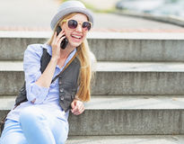 Happy hipster girl talking cell phone while sitting on stairs Royalty Free Stock Photography