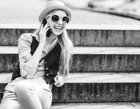 Hipster girl talking cell phone while sitting on stairs stock photo