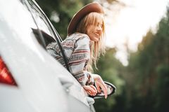 Happy hipster girl traveling adventure vacations. Boho woman sitting in car looking from window on view in country road. Happy hipster girl traveling adventure stock images