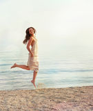 Happy hipster girl walking in sea water. Royalty Free Stock Photos