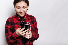 Happy hipster girl wearing red checked shirt holding smartphone in her hands listening to music or audiobook with headphones, rece Stock Photos
