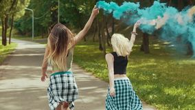 Happy hipster girls in beautiful clothes runs in park waving colored smoke stock video
